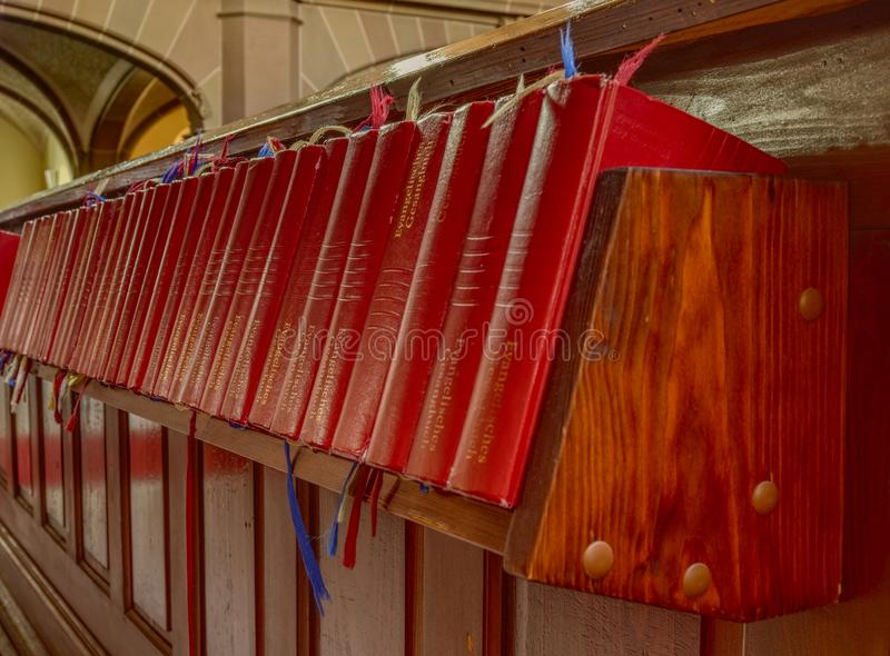 Red bibles on a shelf in a church stock photography