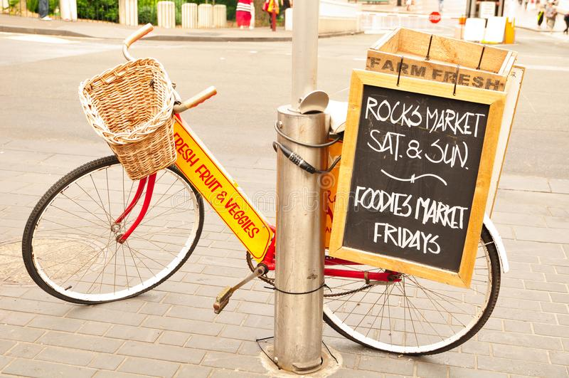 The red bicycle in front of the Rocks Market in Sydney shows the trading hours ` Saturday and Sunday, foodie market on Friday. Sydney, Australia. - On October royalty free stock photo