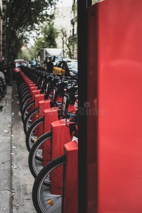 Red bicycles for hire on Barcelona`s public transport system. Barcelona, Spain. 15 April 2019. Bicing - Barcelona`s bicycle hire system, stack of red cycles on stock photography
