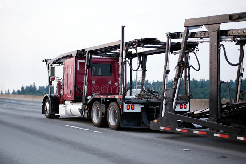 Red big rig classic semi truck car hauler with empty trailer run royalty free stock photo