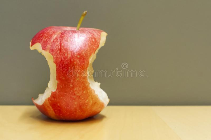 Red bitten apple in a table stock image