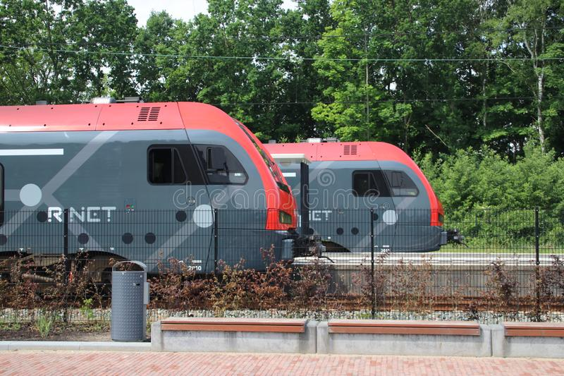 Red and black avenio NS train of R-NET at Boskoop railway station between Gouda and Alphen aan den Rijn in the Netherlands. Red and black avenio NS train of R stock image