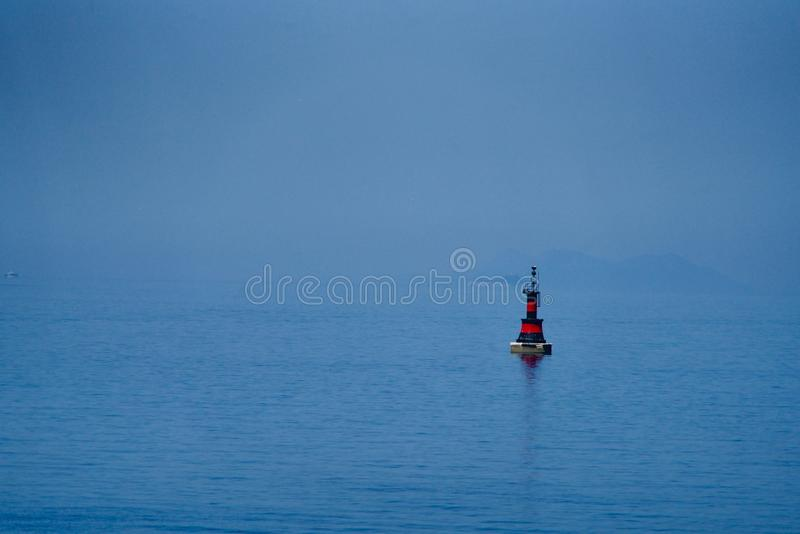 Red-black buoy. In the blue sea royalty free stock photography