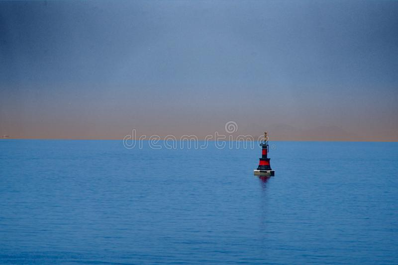 Red-black buoy. In the blue sea stock photos