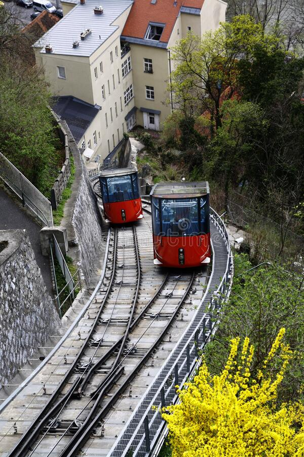 Red and Black Cable Train Uphill Near the Houses during Daytime stock photos