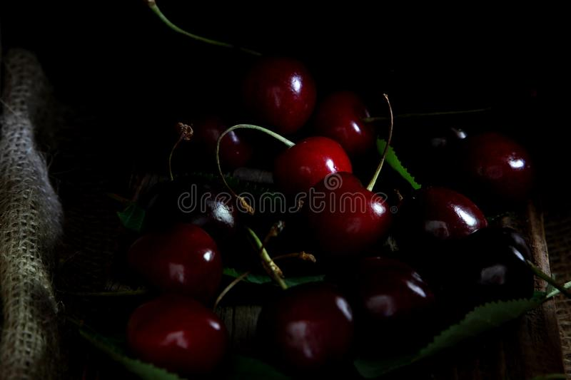 Red and black cherries with leaves on wooden background royalty free stock images