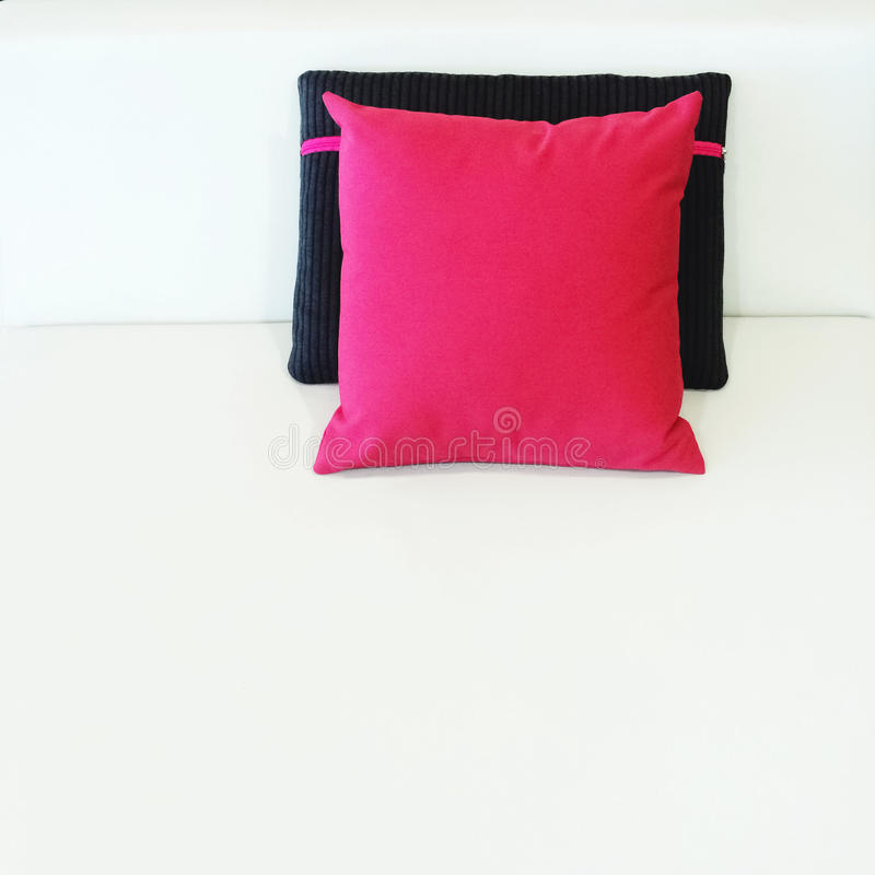 Red and black cushions on a bed. With white sheets royalty free stock image