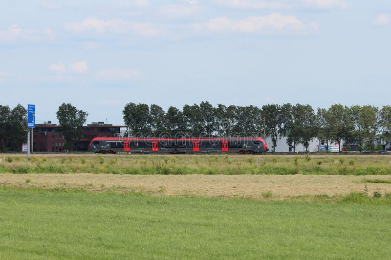 Red and black Flirt train for R-Net on track between Gouda and Alphen aan den Rijn at Waddinxveen royalty free stock photography