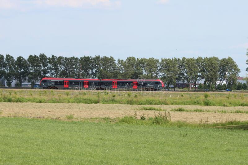 Red and black Flirt train for R-Net on track between Gouda and Alphen aan den Rijn at Waddinxveen stock images