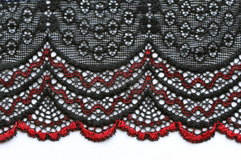 Red and black flowers lace material texture macro shot. Bright red and black flowers lace material texture macro shot royalty free stock images