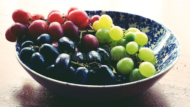 Red, Black, and Green Grapes in Round Blue and White Floral Ceramic Bowl royalty free stock image