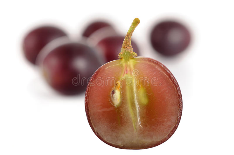 Red black halved grape grapes. Red black halved grape in front of grapes macro royalty free stock images