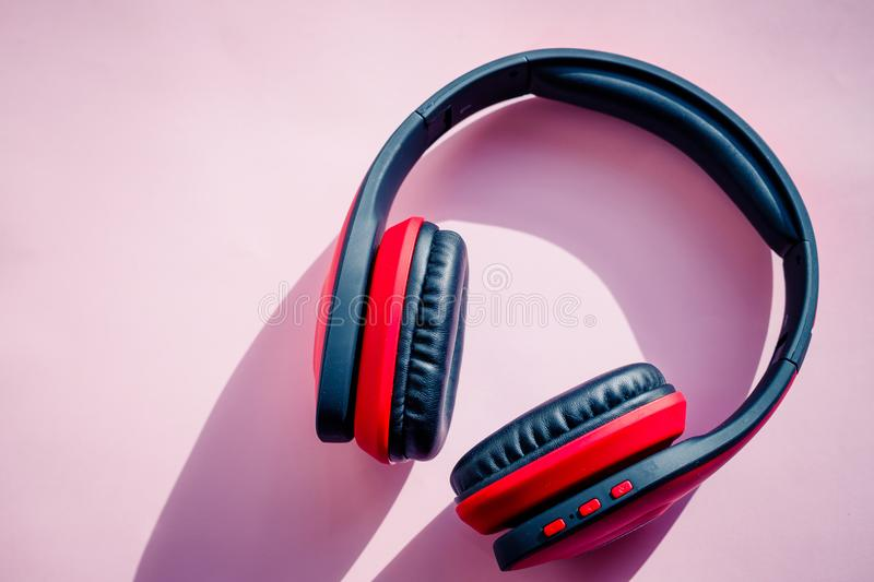 Red and black headphones on pink background. Listen the music. Minimalism idea concept. royalty free stock photography