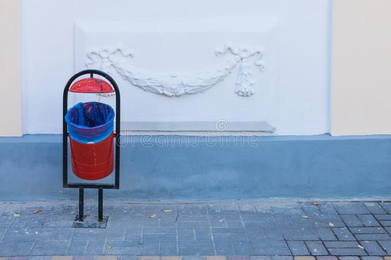 The red and black litter bin on the city or town pavement on the background of white wall with ornament in the sunny day royalty free stock photo