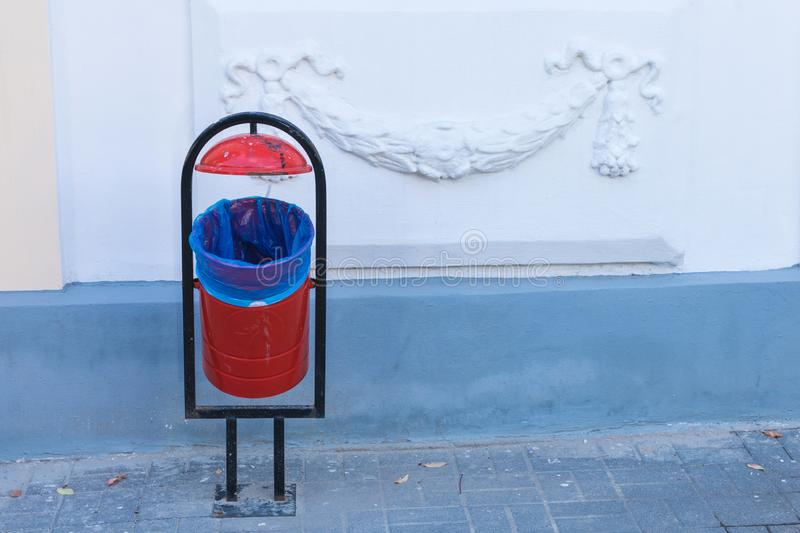 The red and black litter bin on the city or town pavement on the background of white wall with ornament in the sunny day. The red and black litter bin on the stock photos
