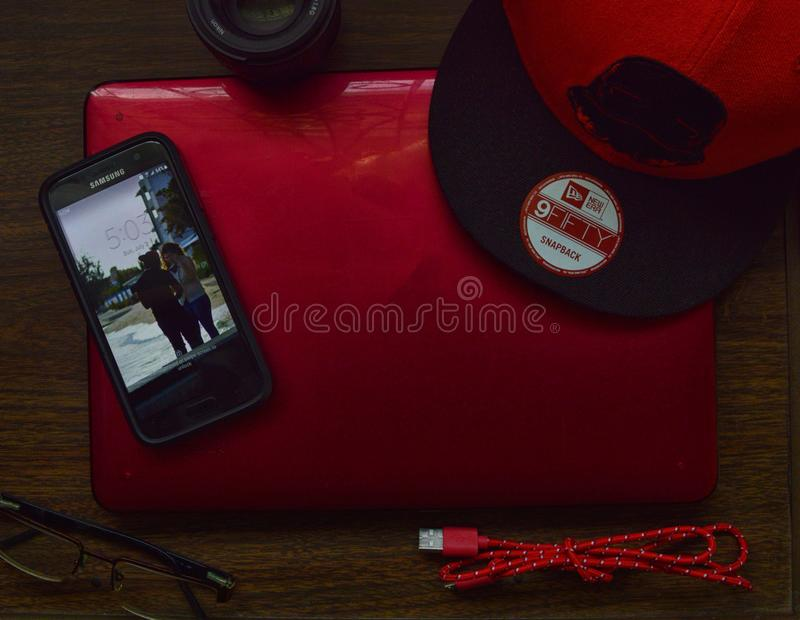 Red and Black New Era 9fifty Snapback Cap and Black Samsung Galaxy Android Smartphone stock photo