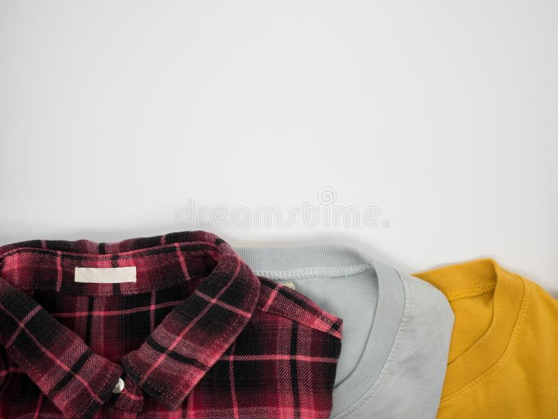 Red-black plaid shirt,grey T shirt and yellow T shirt folded on white background. With copy space stock photo