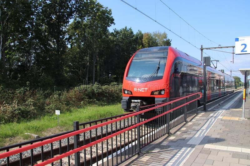 Red and black R-NET light rail train vehicle at the train station of Boskoop stock photos