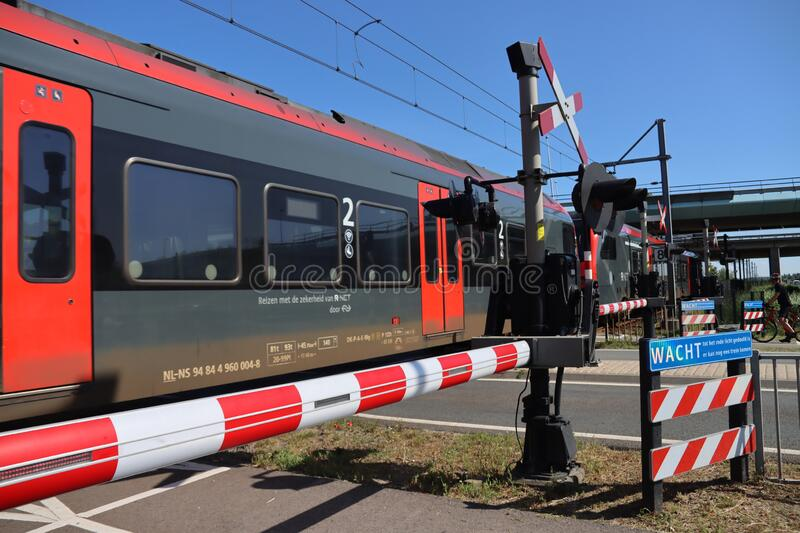 Red and black R-net train at a railroad crossing in Waddinxveen between Alphen aan den Rijn and Gouda stock photo