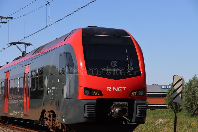 Red and black R-net train at a railroad crossing in Waddinxveen between Alphen aan den Rijn and Gouda stock photos