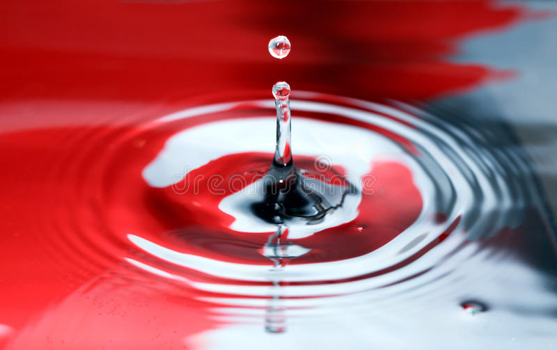 Red And Black Splash. Abstract red and black water splash with drop closeup stock images