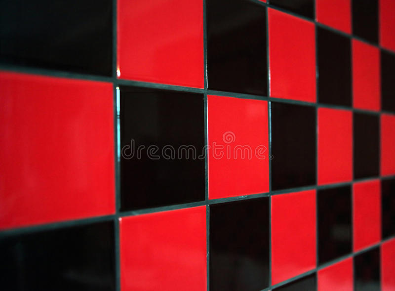 Red and black tile. Wall with a red and black tile. The limited sharpness royalty free stock photos