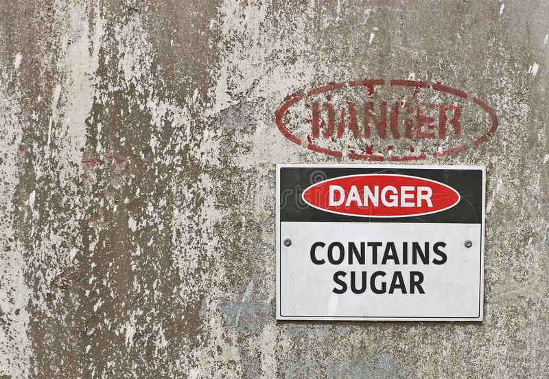 Red, black and white Danger, Contains Sugar warning sign. On industrial concrete background royalty free stock photos