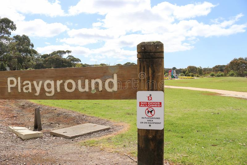 A red, black and white No Dogs Allowed in Playground Area or on. Equipment sign with playground in background stock image