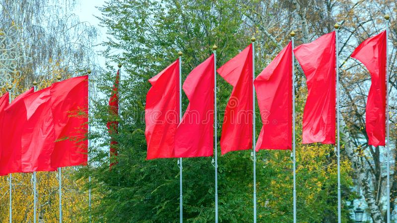 Red blank flags waving in the wind. Against a background of green trees stock photos