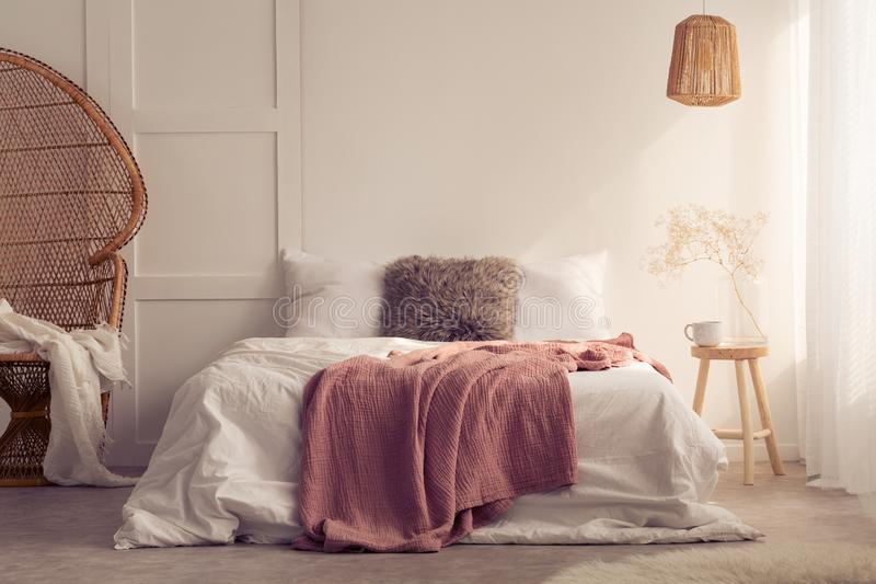 Red blanket on bed with cushions in white bedroom interior with lamp and rattan chair. Real photo royalty free stock photography