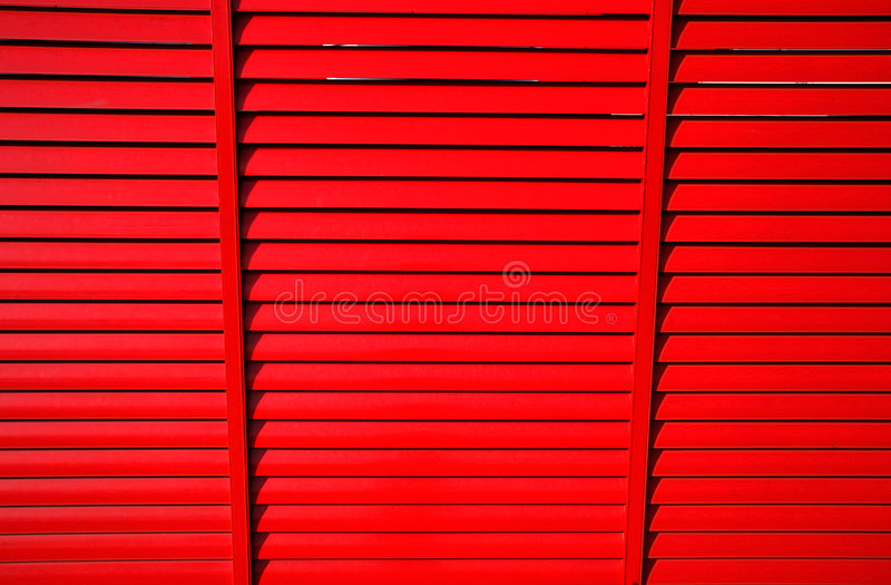 Red blinds. Red metal venetian blind separation wall on building rooftop stock photography