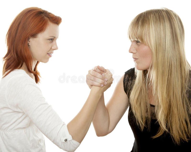 Red and blond haired girls battle each other. Young beautiful red and blond haired girls in front of white background stock image