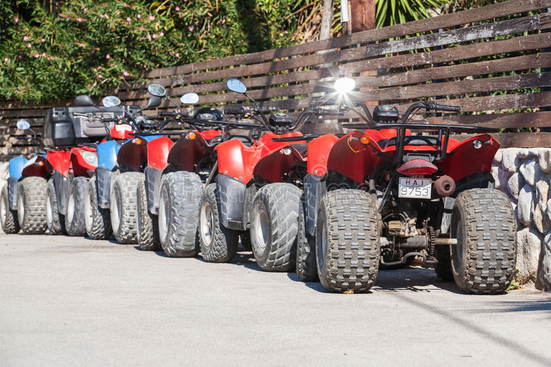 Red and blue atv quad bikes. Zakynthos, Greece - August 14, 2016: Red and blue atv quad bikes stand parked in a row on roadside. Popular tourist mode of stock images