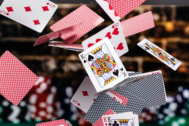 Red and Blue backed Playing cards cascading in front of a background of stacked poker chips stock photos