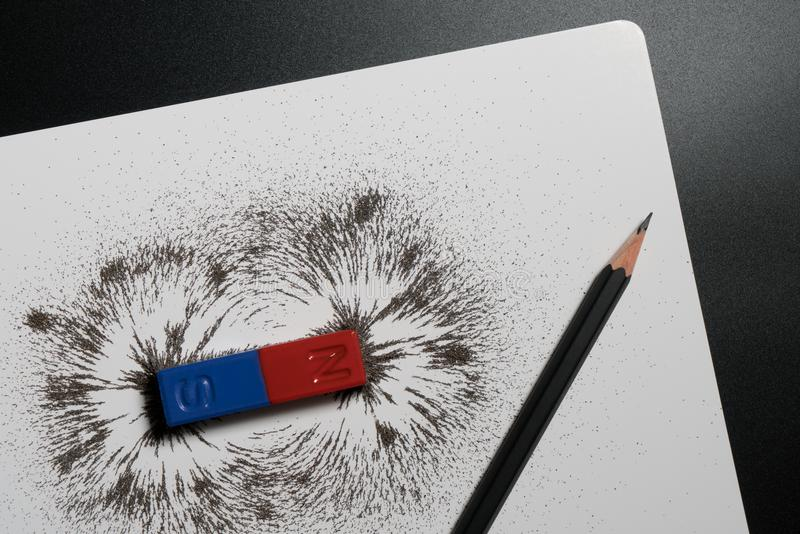 Red and blue bar magnet or physics magnetic, pencil and iron pow stock photos