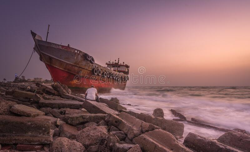 Red Blue and Black Photo of a Ship and a Man Sitting on a Stone Near Seashore royalty free stock images
