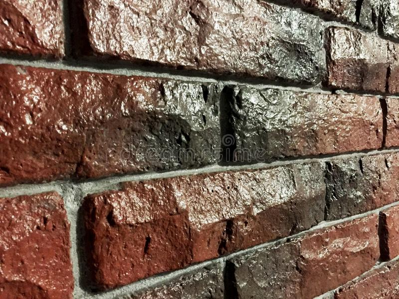 Red-blue brick wall covered with glossy lacquer with embroidery. Interior old wall stock photography