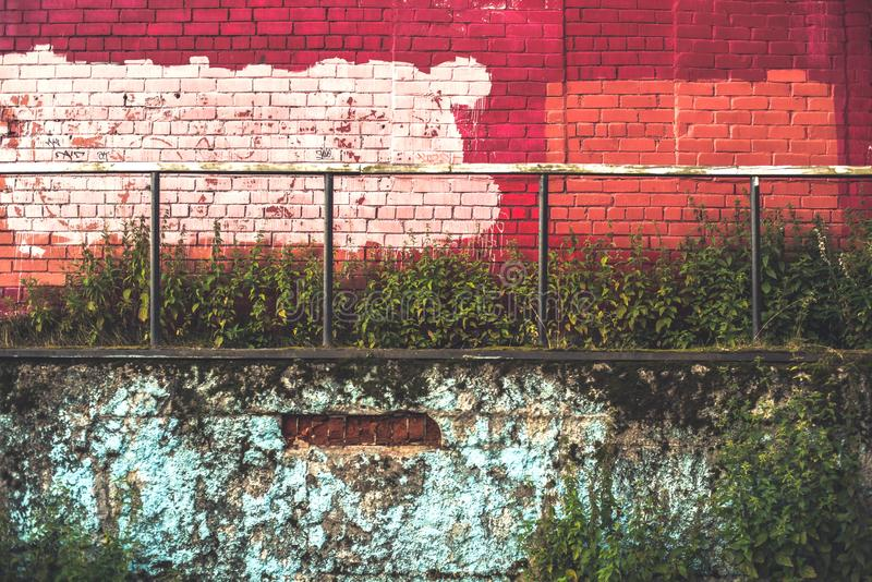 Red and blue brick wall with an iron handrail. Overgrown with a grass and a nettle royalty free stock photography