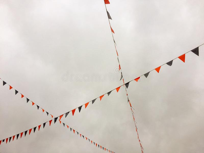 Red and blue bunting flags strung overhead. Red and blue bunting flags strung overhead against a dreary bleak sky stock photos