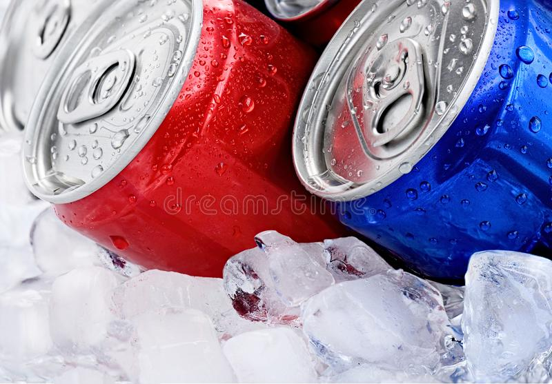 Red and blue cans with droplets on ice cube stock photo