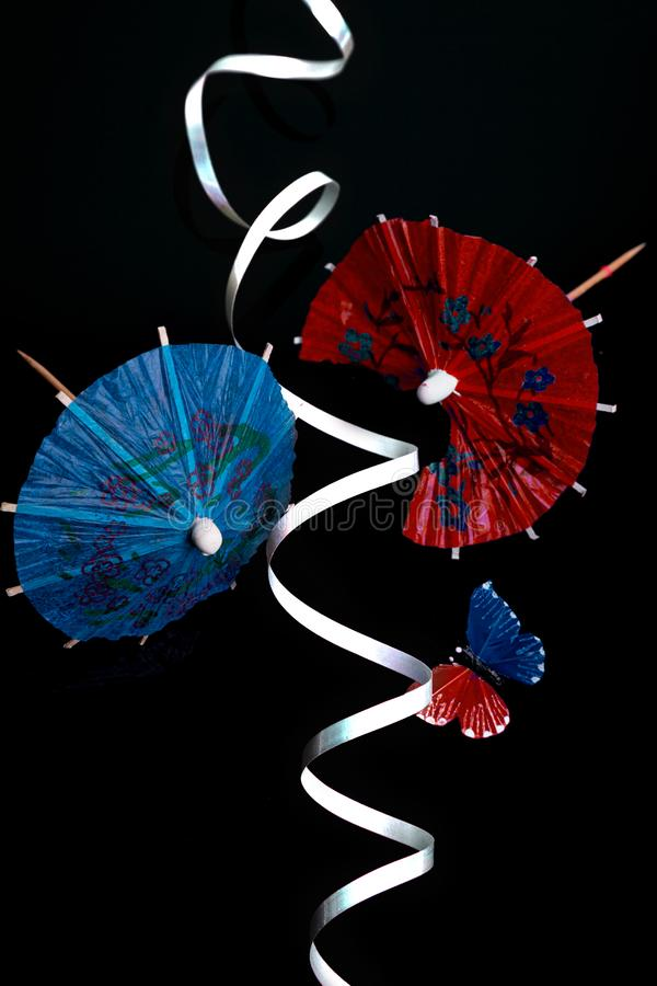 Red and Blue Cocktail Umbrellas with butterfly and ribbon royalty free stock photos