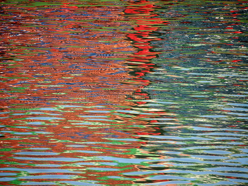 Red Blue Color pattern shimmers and reflects in ripples of water. Making a psychedelic pattern royalty free stock photo