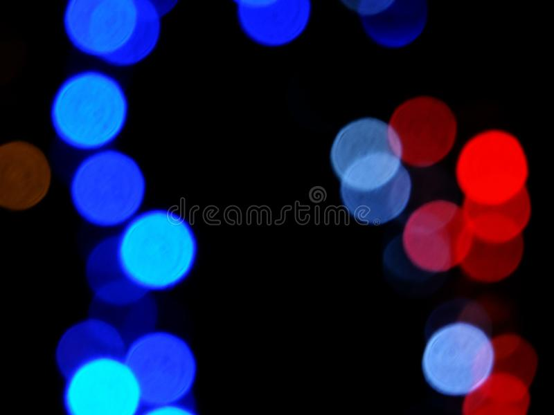 Red and blue decorative glowing blurred lights night background. On black stock image