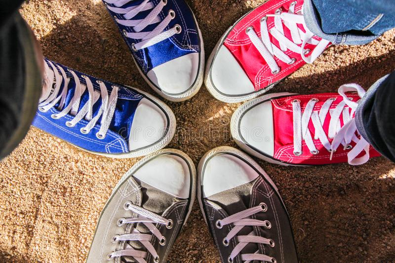 Red, blue and gray sneakers standing in the circle on dry sand, view from above . Friendship, fashion, lifestyle and adventure con royalty free stock image