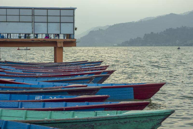 A red blue green wooden boats at the pier on the water in cloudy weather. lake on the background of the mountains. Red blue green wooden boats at the pier on the royalty free stock image
