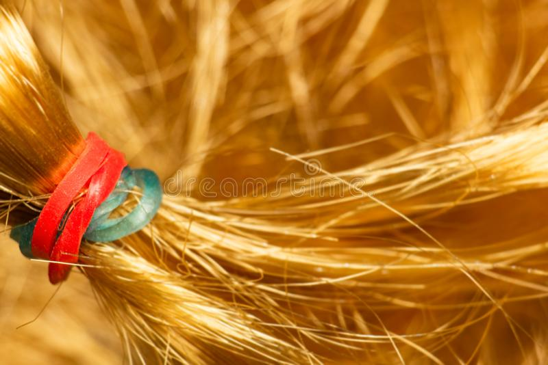 Red and blue hair tie for hair on bright yellow artificial hair stock images