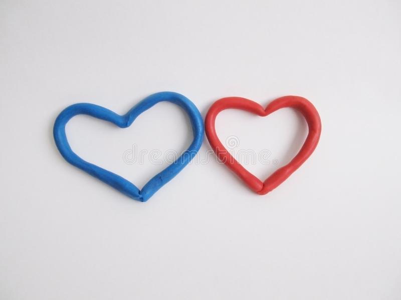 Red and blue heart. Romantic background from red hearts on a light background stock images