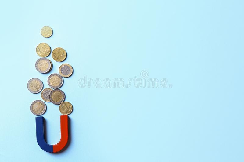 Red and blue horseshoe magnet attracting coins on light blue background. Flat lay. Space for text royalty free stock photos