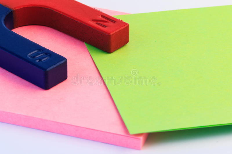 Red and blue horseshoe magnet on paper note. stock image