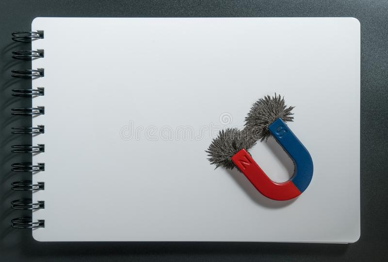 Red and blue horseshoe magnet or physics magnetic and compass with iron powder magnetic field on white paper notebook background. royalty free stock images